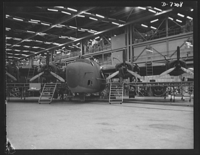 Production. B-24 bombers and C-87 transports. The assembly line, in which consolidated transport ships are made in a Western aircraft plant, moves to another station. This new transport plane, adapted from the famous B-24 bomber, is known as C-87, and carries one of the greatest human or cargo loads of any plane now in mass production