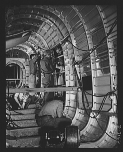 Production. B-24 bombers and C-87 transports. The cargo door of a consolidated transport plane is fitted into a tail fuselage opening at a Western aircraft plant. This new transport, an adaptation of the B-24 bomber, is known as C-87, and carries one of of the greatest human or cargo loads of any plane now in mass production. It is built in a plant equipped with the best and most modern air conditioning and fluorescent lighting systems