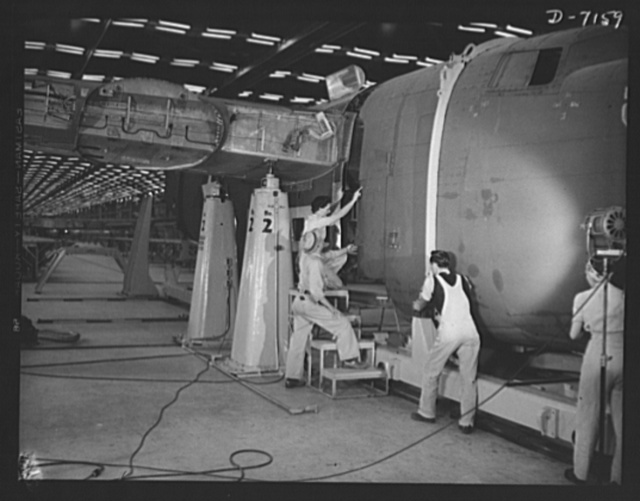 Production. B-24 bombers and C-87 transports. The nose section of a mighty consolidated transport plane, goes into place in the fuselage mating fixture of a Western aircraft plant. This new transport, an adaptation of the B-24 bomber, is known as the C-87, and carries one of the greatest human or cargo loads of any plane now in mass production. It is built in a plant equipped with the best and most modern air conditioning and fluorescent lighting systems in the country