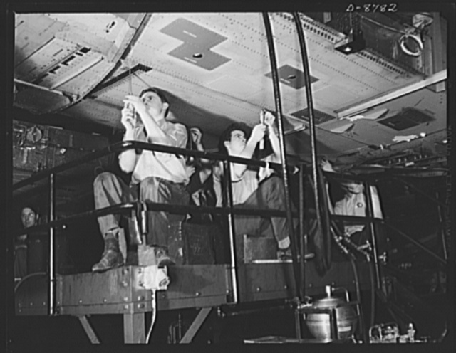 Production. B-24E (Liberator) bombers at Willow Run. Working on a center wing section for a B-24E (Liberator) bomber after it has been placed on one of the assembly lines at Ford's big Willow Run plant. The Liberator is capable of operation at high altitudes and over great ranges on precision bombing missions. It has proved itself an excellent performer in the Pacific, in Northern Africa, Europe and the Aleutians. Ford's Willow Run Plant, Michigan