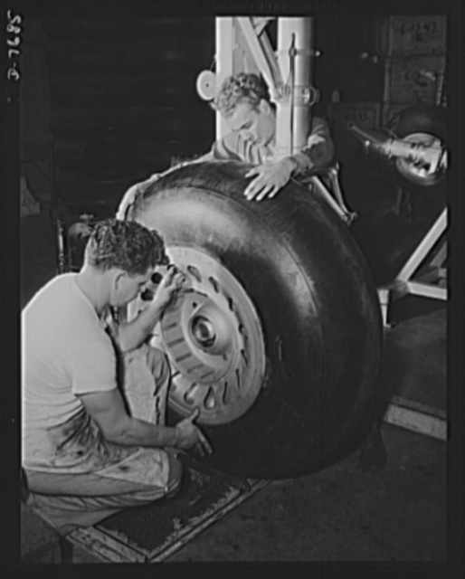 "Production. B-25 ""Billy Mitchell"" bombers. A huge rubber tire is mounted on the landing gear strut of a B-25 bomber before it moves to the final assembly line of North American's Inglewood, California, plant. In addition to the battle-tested B-25 ""Billy Mitchell"" bomber, in General Doolittle's raid on Tokyo, this plant produces the P-51 ""Mustang"" fighter plane which was first brought into prominence by the British raid on Dieppe"