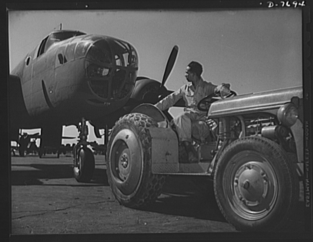 """Production. B-25 """"Billy Mitchell"""" bombers. A Negro employee at the flight ramp of North American's Inglewood, California, plant, tows a B-25 bomber into place. In addition to the battle-tested B-25 """"Billy Mitchell"""" bomber, used in General Doolittle's raid on Tokyo, this plant produces the P-51 """"Mustang"""" fighter plane which was first brought into prominence by the British raid on Dieppe"""