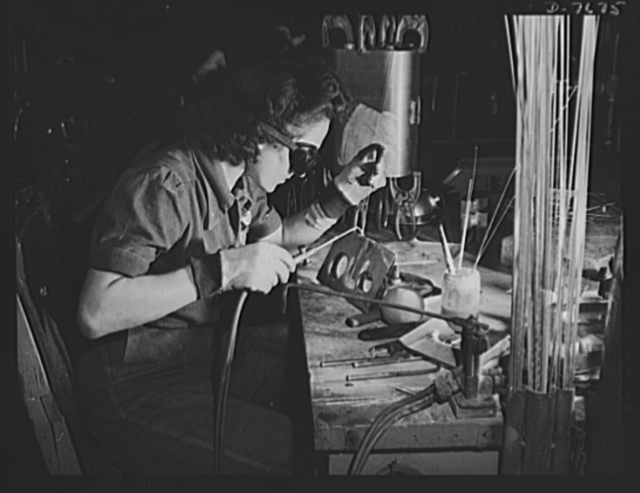 """Production. B-25 """"Billy Mitchell"""" bombers. A woman welder at the Inglewood, California, plant of North American Aviation works on a sub-assembly for one of the huge tanks that go into B-25 bombers. In addition to the battle-tested B-25 """"Billy Mitchell"""" bomber, used in General Doolittle's raid on Tokyo, this plant produces the P-51 """"Mustang"""" fighter plane which was first brought into prominence by the British raid on Dieppe"""