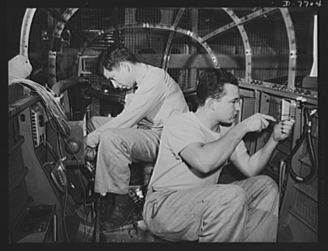 "Production. B-25 ""Billy Mitchell"" bombers. In the bombardier's compartment of a B-25 bomber, North American employees assemble the electrical system as the section moves down the long conveyor line at Inglewood, California, In addition to the battle-tested B-25 ""Billy Mitchell"" bomber, used in General Doolittle's raid on Tokyo, this plant produces the P-51 ""Mustang"" fighter plane which was first brought into prominence by the British raid on Dieppe"