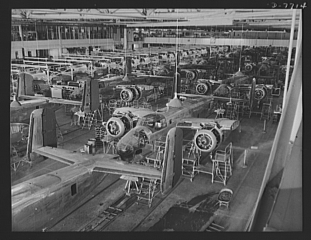 "Production. B-25 ""Billy Mitchell"" bombers. Partial view of one of North American Aviation's B-25 bomber assembly lines at Inglewood, California. When the planes move out the door, they are ready for painting and flight tests. In addition to the battle tested B-25 ""Billy Mitchell"" bomber, used in General Doolittle's raid on Tokyo, this plant produces the P-51 ""Mustang"" fighter plane which was first brought into prominence by the British raid on Dieppe"