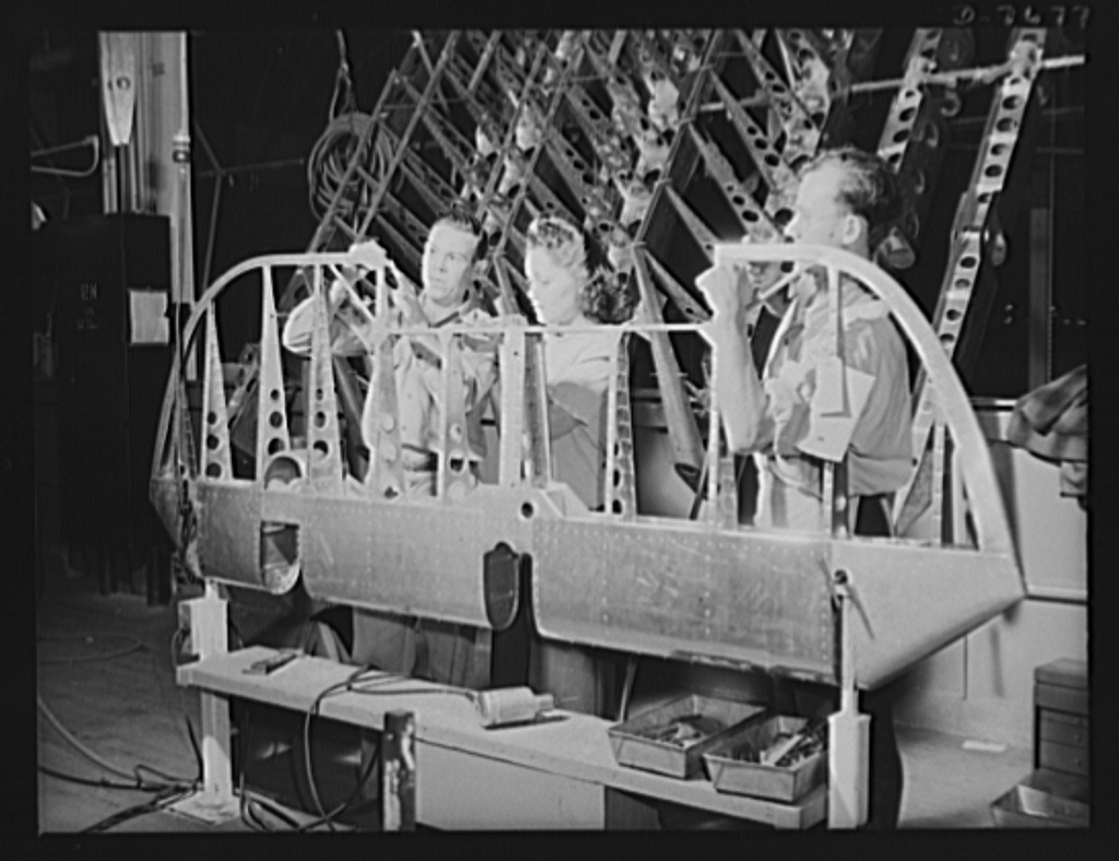 """Production. B-25 """"Billy Mitchell"""" bombers. The metal structure for a rudder on a B-25 bomber is assembled by North American employees in the control surface department at Inglewood, California. The part will next move to the covering department for its fabric cover. Women are fast taking the places of men in this department. In addition to the battle-tested B-25 (""""Billy Mutchell"""") bomber used in General Doolittle's raid on Tokyo, this plant produces the P-51 """"Mustang"""" fighter plane which was first brought into prominence by the British raid on Dieppe"""