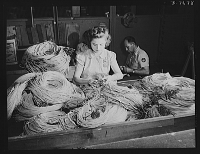 "Production. B-25 ""Billy Mitchell"" bombers. Thousands of feet of insulated conductor wire that go into a North American B-25 bomber are sorted by this woman employee in the electrical assembly department at Inglewood, California. In addition to the battle-tested B-25 ""Billy Mitchell"" bomber, used in General Doolittle's raid on Tokyo, this plant produces the P-51 ""Mustang"" fighter plane which was first brought into prominence by the British raid on Dieppe"