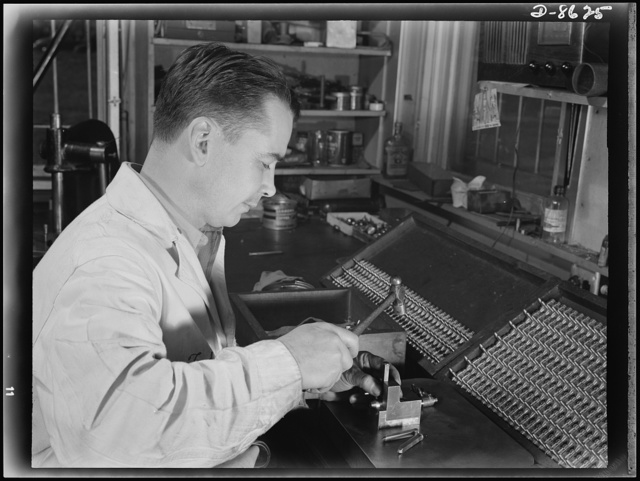 Production. Blood transfusion bottles. Employed by a local subcontractor for Baxter Laboratories Inc., Glenview, Illinois, Theodore G. Coffin, a former auto mechanic numbers the barrels of the valves for blood transfusion bottles prepared by Baxter's for use in blood banks