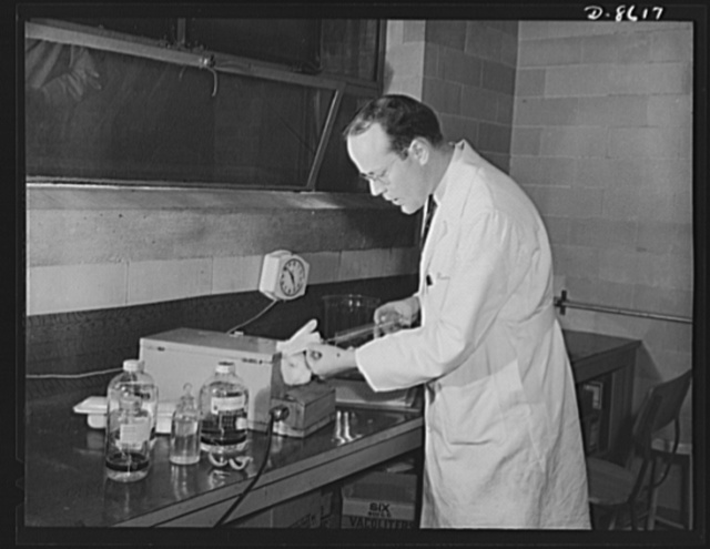 Production. Blood transfusion bottles. Rabbits too, aid the war effort. William Edwin Morris, histologist for Baxter Laboratories Inc., Glenview, Illinois, conducts research on blood plasma through experimentation on rabbits. The company prepares transfusion bottles for blood letting
