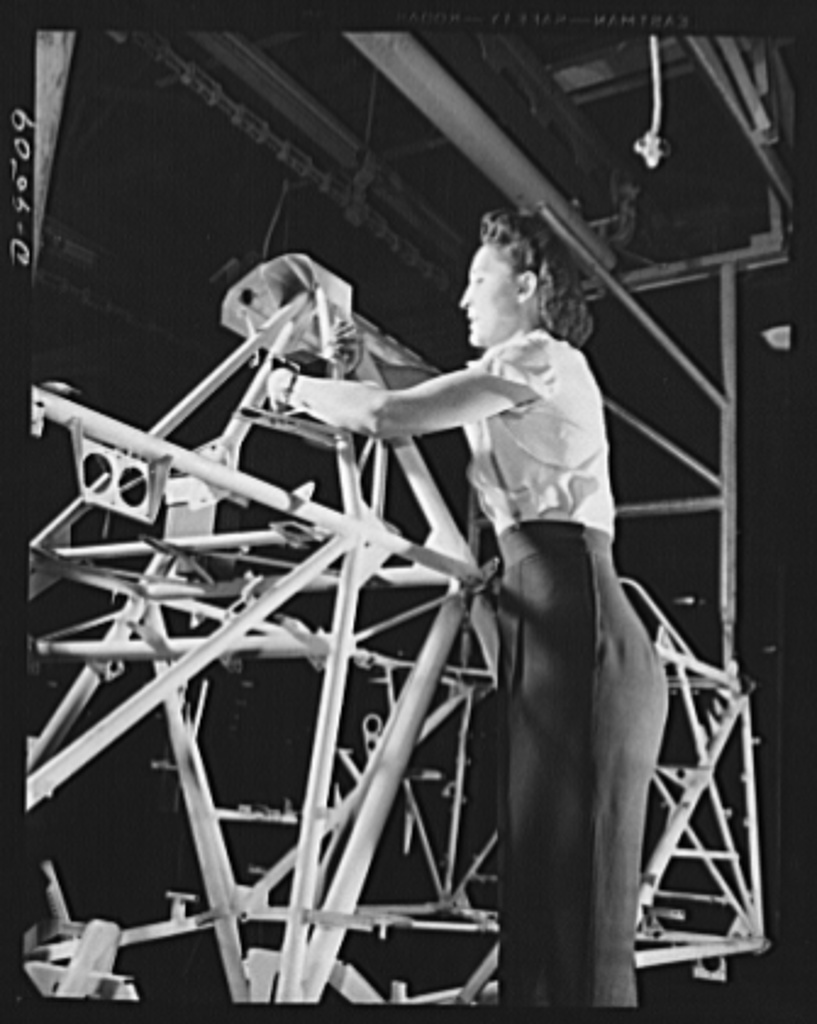 """Production. BT-13A (""""Valiant"""") basic trainers. A woman employee at Vultee's Downey, California plant works on a fuselage frame for a """"Valiant"""" basic trainer. At the Downey plant is made the BT-13A (""""Valiant"""") basic trainer--a fast, sturdy ship powered by by a Pratt and Whitney Wasp engine"""