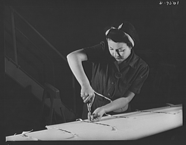 "Production. BT-13A (""Valiant"") basic trainers. Ailerons on ""Valiant"" basic trainers are fabric-covered. A woman worker at Vultee's Downey, California plant performs a stitching operation. At the Downey plant is made the BT-13A (""Valiant"") basic trainer--a fast sturdy ship powered by a Pratt and Whitney Wasp engine"