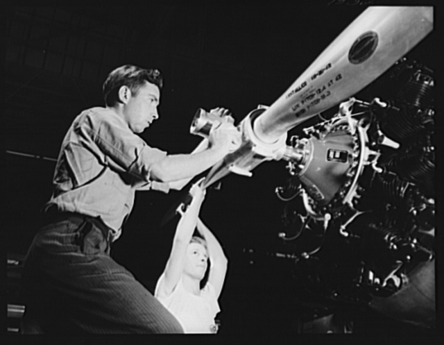 """Production. BT-13A (""""Valiant"""") basic trainers. Installation of the propellor of a """"Valiant"""" basic trainer on the Vultee assembly line at Downey, California. Propellors are Hamiltons. At the Downey plant is made the BT-13A (""""Valiant"""") basic trainer--a fast, sturdy ship powered by a Pratt and Whitney Wasp engine"""