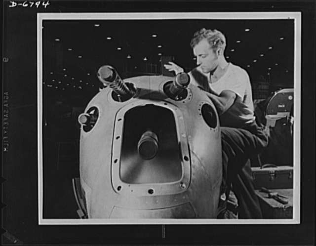"""Production. Lockheed P-38 pursuit plane. An armorer's assistant in a large Western aircraft plant works on the installation of one of the machine guns in the nose section of a new Lockheed P-38 pursuit plane. This nose section will later be """"mated"""" to a center section and the plane body will travel down a main assembly line where wings, engines, and other essential equipment will be installed"""
