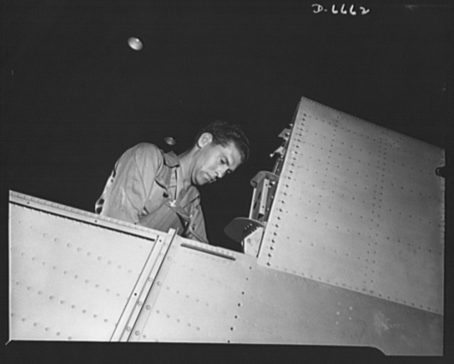 Production. Lockheed P-38 pursuit planes. A mechanic in a large Western aircraft plant at work on a center section for a Lockheed P-38 pursuit plane. On a final assembly line, the completed center section will be joined to other plane sections, and noses, engines, wings, landing gear and other equipment will be installed