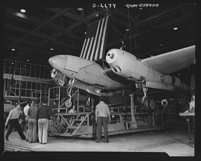 Production. Lockheed P-38 pursuit planes. A new Lockheed P-38 pursuit plane, complete except for propellers, is hoisted from a station stand in a large Western aircraft plant assembly line. From here, the ship will be rolled to the testing field where the propellers will be installed and trial flights will be made