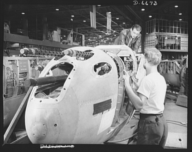 "Production. Lockheed P-38 pursuit planes. An armorer and his assistant check machine gun controls in a nose section of a new Lockheed P-38 pursuit ship. The guns are cocked and simulated firing is conducted to assure perfect operation of the control and selector systems. This nose section will later be ""mated"" to a center section and the partly-finished ship will travel down the main assembly line to receive engines, wings, landing gear and other essential equipment"