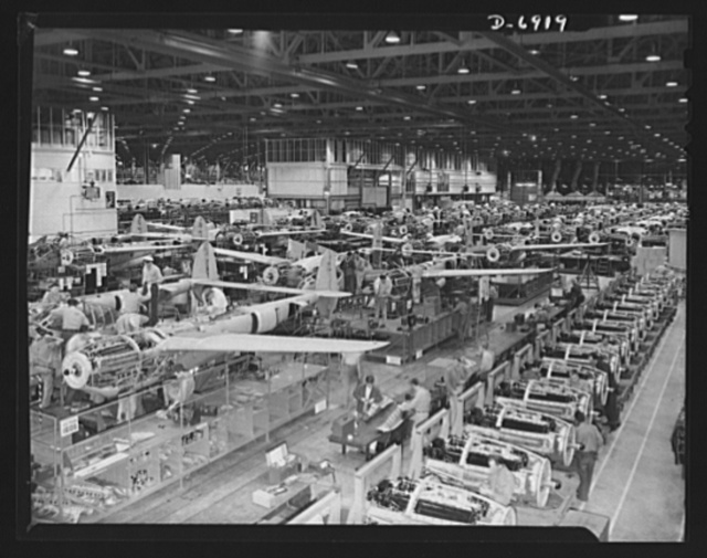 "Production. Lockheed P-38 pursuit planes. Overall assembly line for Lockheed P-38 pursuit planes. A row of Allison engines reaches back from the right foreground. Under the American flag in the left background is the ""Lightning"" assembly line, a duplicate of the P-38 line"