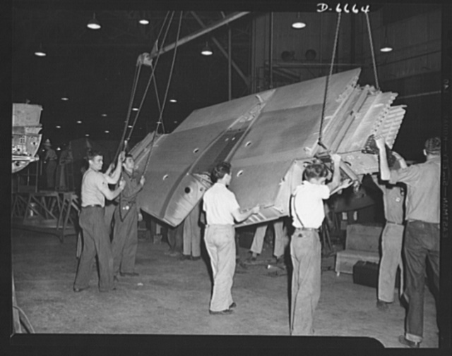 "Production. Lockheed P-38 pursuit planes. The center section for a Lockheed P-38 pursuit ship ready to go into a ""mating"" jig at a large Western aircraft plant. In the ""mating"" operation, nose sections and other plane members are joined to the center section. The partly-finished plane body is then ready to travel down the main assembly line where engines, wings, and other essential equipment will be installed"
