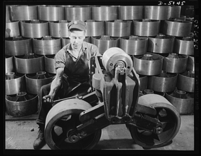 Production. M-4 tanks. Mighty M-4 tanks are flowing in a strong, steady stream from the production lines of our arsenal of democracy. These bogie wheels being assembled in an Eastern plant give some idea of the massive construction of our new land battleships