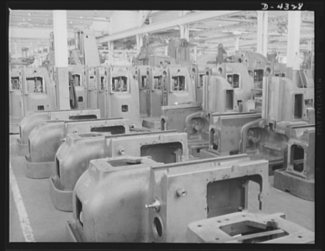 Production. Milling machines and machine castings. Milled, bored and with their V-shaped bearings carefully scraped to provide smooth sliding ways for other parts, this forest of machine tool castings waits at the head of the assembly lines. An idea of the variety of shapes and sizes is evident here