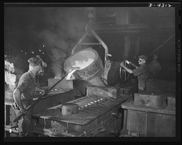 Production. Milling machines and machine castings. Pouring a large mold is a fiery sight. To the left, flames are shooting from an escape hole -- caused by gas generated by the contact of iron with the relatively cool sand, graphite, linseed oil and other ingredients involved in the mold structure. The man at the left is wielding a skimmer to hold back any impurities floating on the surface of the ladle iron
