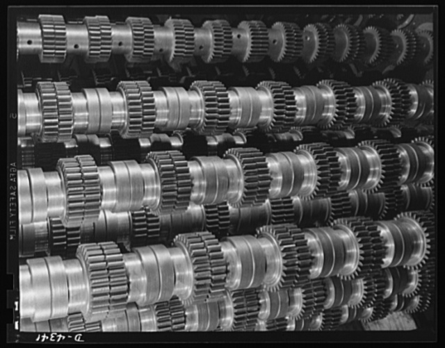 Production. Milling machines and machine castings. These are spur gears piled up at a large Midwest machine tool plant producing highly essential equipment for making various war materials