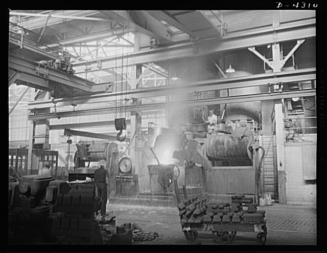 Production. Milling machines and machine castings. This picture shows the general setup on the foundry floor. Notice the overlapping cranes (above and left). Any one of four cranes can come in to pick up full ladles, depending on their size and destination. Location: a large Midwest machine tool foundry