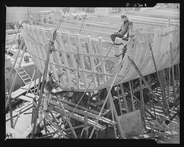 Production. Minesweepers. Stern view of the frame of a new minesweeper under construction in an Eastern shipyard. After the sturdy ribs have been planked over and a power plant installed, the hull will be ready for launching. Gibbs Cass Company