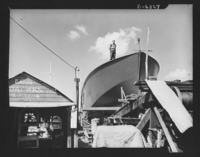 Production. Motor torpedo boats (wooden). A Coast Guard sentry stands watch over a new torpedo boat under construction at a Southern shipyard. In addition to wooden torpedo boats, the yard also turns out many steel boats for the Navy. Higgins Industries