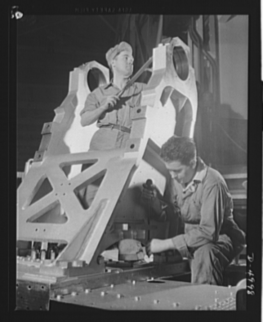 Production. Naval gun mounts. The chassis of a large naval gun mount nears completion as workmen of a Midwest machine shop perform final scraping and fitting operations. Westinghouse, Louisville