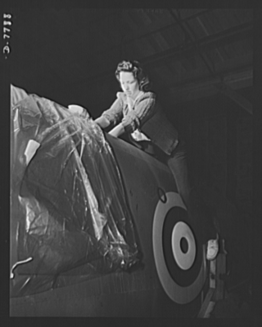 """Production. P-51 """"Mustang"""" fighter planes. A North American Aviation woman employee at Inglewood, California, sits astride a """"Mustang"""" fighter for Royal Air Force (RAF), as she places a bag of chemicals in the plane to prevent the accumulation of moisture. This plant produces the battle-tested B-25 """"Billy Mitchell"""" bomber, used in General Doolittle's raid on Tokyo, and the P-51 fighter plane which was first brought into prominence by the British raid on Dieppe"""