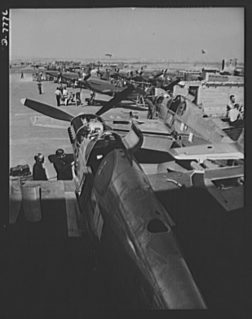 """Production. P-51 (""""Mustang) fighter planes. A partial view of North American's flight ramp at Inglewood, California. In the foreground is a P-51 fighter which has just rolled off the final assembly line. It is now awaiting its coat of war paint. This plant produces the battle-tested B-25 (""""Billy Mitchell"""") bomber, used in General Doolittle's raid on Tokyo, and the P-51 fighter plane which was first brought into prominence by the British raid on Dieppe"""