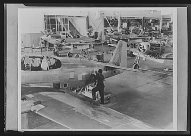 """Production. P-51 (""""Mustang) fighter planes. An inspector checks over the work done on a P-51 fighter before it moves to the next assembly position at North American's Inglewood, California, plant. This plant produces the battle-tested B-25 (""""Billy Mitchell"""") bomber, used in General Doolittle's raid on Tokyo, and the P-51 fighter plane which was first brought into prominence by the British raid on Dieppe"""