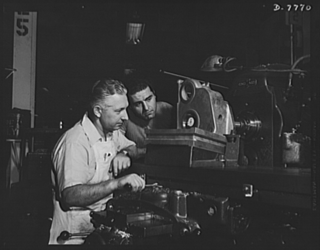 """Production. P-51 """"Mustang"""" fighter planes. The accuracy of a milling machine operation is checked by an inspector in a machine shop at the Inglewood, California, plant of the North American Aviation. The casting being milled will be part of the landing gear of a P-51 fighter plane. This plant produces the battle-tested B-25 """"Billy Mitchell"""" bomber, used in General Doolittle's raid on Tokyo, and the P-51 fighter plane which was first brought into prominence by the British raid on Dieppe"""