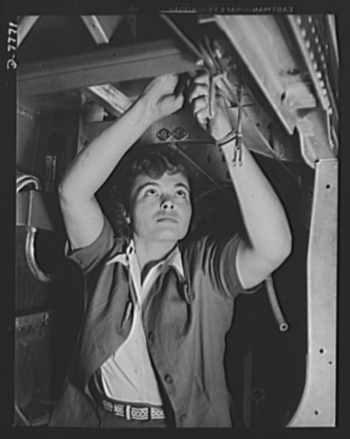 """Production. P-51 """"Mustang"""" fighter planes. This woman employee at the Inglewood, California, plant of the North American Aviation, assembles control cables inside the fuselage of a P-51 fighter. This plant produces the battle-tested B-25 """"Billy Mitchell"""" bomber, used in General Doolittle's raid on Tokyo, and the P-51 fighter plane which was first brought into prominence by the British raid on Dieppe"""