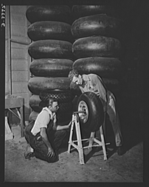 """Production. P-51 (""""Mustang) fighter planes. Two employees at North American's Inglewood, California, plant, test the balance of a mounted tire for a P-51 fighter. In the background are tires for B-25 bombers. This plant produces the battle-tested B-25 (""""Billy Mitchell"""") bomber, used in General Doolittle's raid on Tokyo, and the P-51 fighter plane which was first brought into prominence by the British raid on Dieppe"""