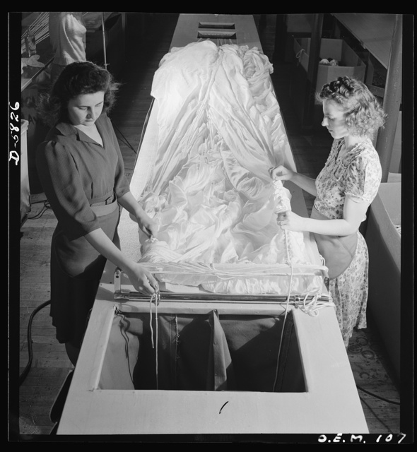 Production. Parachute making. As these two girls thread shroud cords through the material, these yards of silk become more nearly recognizable as one of the parachutes turned out by this Eastern plant. Pioneer Parachute Company, Manchester, Connecticut