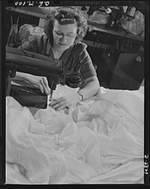 Production. Parachute making. Every stitch on this basting machine means as much to Eva Matties as the parachutes she is sewing may mean to her fiance in the Army. Miss Matties also has two brothers in the service, one stationed at an air base, the other in an aircraft carrier somewhere in the Pacific. Pioneer Parachute Company, Manchester, Connecticut