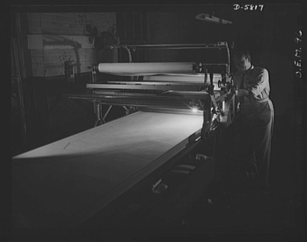 Production. Parachute making. Rolls of silk, destined for action as parachutes for the U.S. Air Force, shown here on the laying-out and cutting table of an Eastern manufacturing plant. The folder machine folds layer upon layer of silk for the cutting operation. Pioneer Parachute Company, Manchester, Connecticut