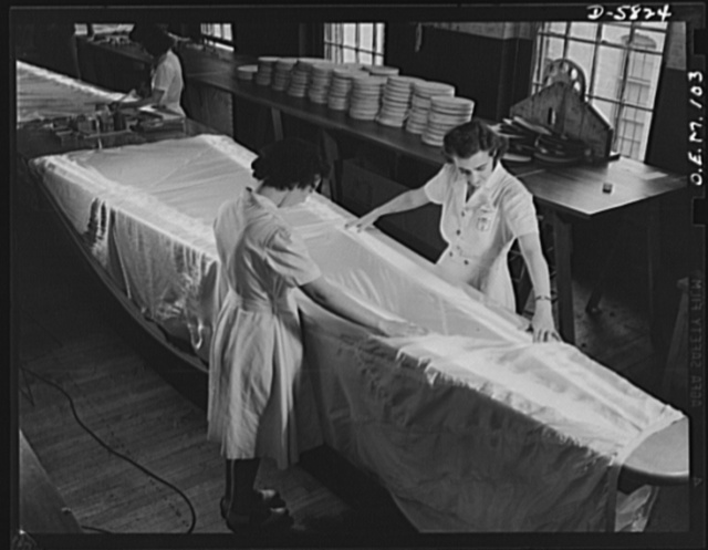 Production. Parachute making. Though it looks like a skirt on an ironing board, this is really a parachute stretched over a glass table, upon which it is subjected to rigid inspection. Electric lights underneath the table show up the slightest imperfection. Pioneer Parachute Company, Manchester, Connecticut