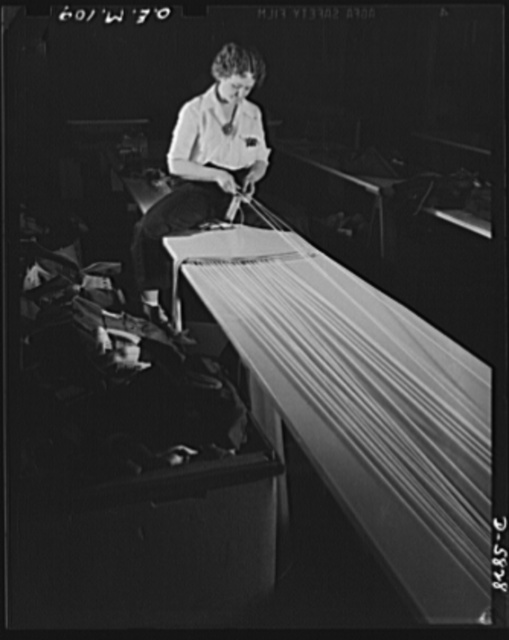 Production. Parachute making. Two of her brothers are in the Army, two brothers are World War I veterans. Perhaps that's why Bonnie Bonness finds attaching shroud cords to parachute straps in this Eastern factory more important than her former profession: dancing in New York's Greenwich Village nightclubs. Pioneer Parachute Company, Manchester, Connecticut