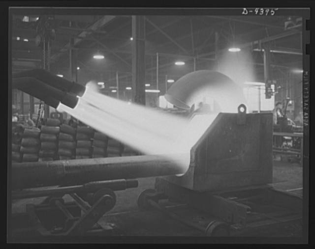 Production. Pipe fittings. Large pipe elbows for the Army are formed in a Midwest plant by heating lengths of pipe with gas flames and forcing them around a die. Tube Turn Incorporated