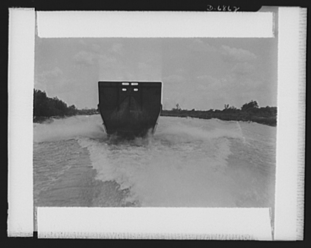 Production. Small ramp boats. A thirty-six-foot wooden ramp boat, just completed at a Southern shipyard, in tow of a fast power launch. The high bottom-hinged stern of this boat is used as a ramp to make beach landings of men and equipment. Higgins Industries
