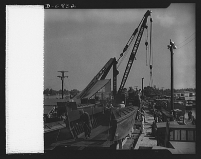 Production. Small ramp boats. Fitting and painting small wooden ramp boats at a Southern shipyard. These thirty-six-foot carriers, built of prefabricated sections, are used for making beach landings of men and equipment. The completed boats are launched by crane and delivered in tows of six to eight. Higgins Industries
