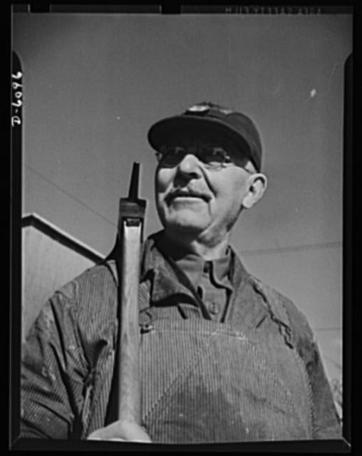 Production. Submarine chasers. An adzeman, master of an ancient craft. Christopher Christophersen, sixty-five, still puts in a full day at an Eastern boatyard shaping oak keels for subchasers. Marine Construction Company, Stamford, Connecticut