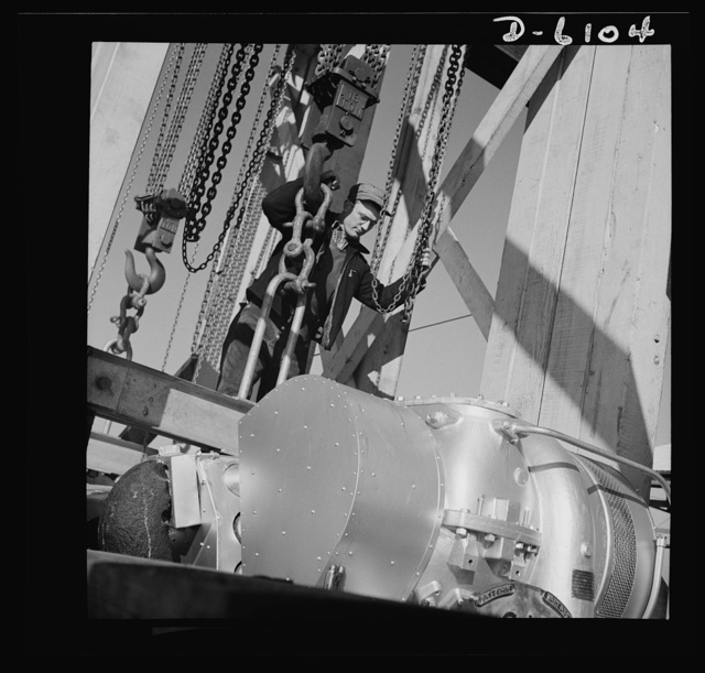 Production. Submarine chasers. Bad news for U-boats. A powerful marine diesel engine is lowered to its bed in the hull of a 173-foot steel subchaser at an Eastern boatyard. Marine Construction Company, Stamford, Connecticut