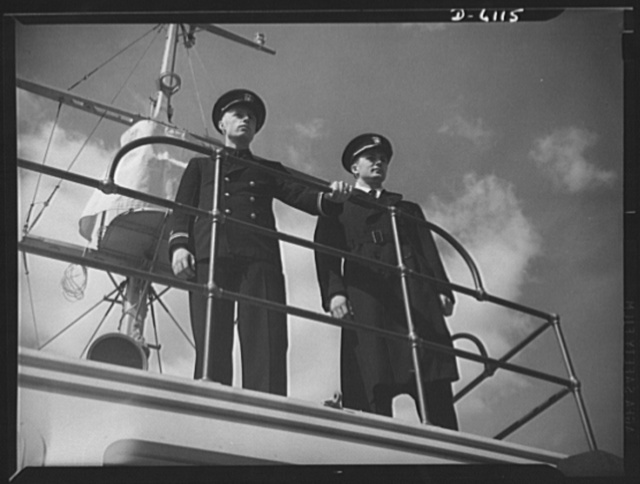 Production. Submarine chasers. Nemesis of the U-boat. A Navy skipper and executive officer stand on the bridge of their new command, a nearly completed 110-foot wooden subchaser that will soon leave an Eastern boatyard. Marine Construction Company, Stamford, Connecticut