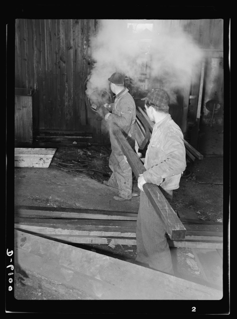 Production. Submarine chasers. Steaming a wooden section for a subchaser under construction at an Eastern boatyard. The wood, blackened by the steam, can now be bent to the required shape. Marine Construction Company, Stamford, Connecticut