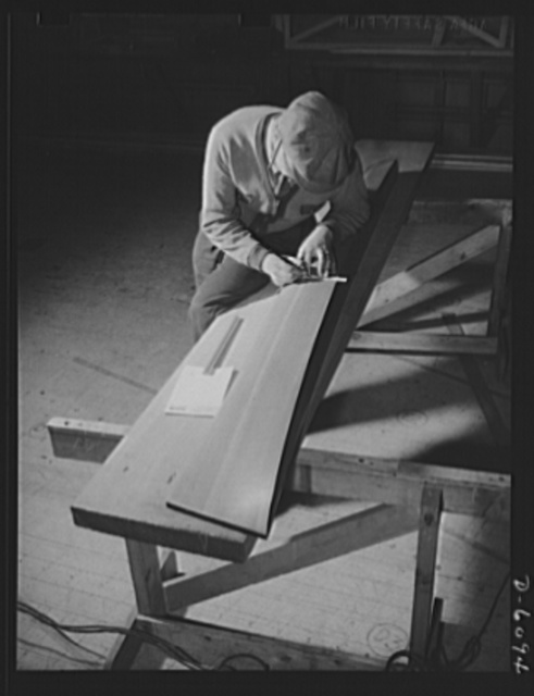 """Production. Submarine chasers. """"Taking off"""" the lines of a 173-foot steel subchaser at an Eastern boatyard. This accurate scale model of half of the hull will determine the lines of the full-size boat. Marine Construction Company, Stamford, Connecticut"""