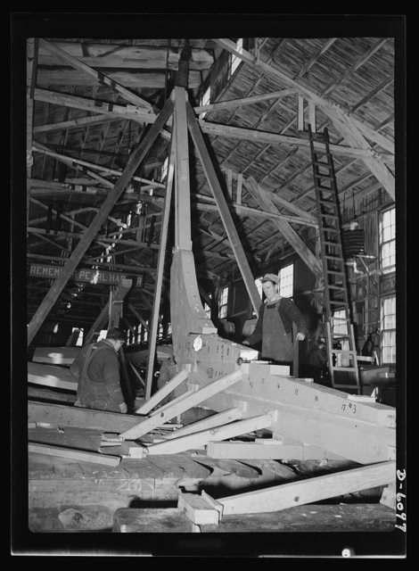 """Production. Submarine chasers. The sturdy oak keel of a wooden subchaser is laid at an Eastern boatyard. The stern of the vessel is scarfed to it. The numbers showing along the keel indicate the """"stations"""" or hull sections into which every boat plan is divided. Marine Construction Company, Stamford, Connecticut"""